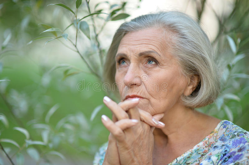 Nice sad old woman. On the autumn background stock images