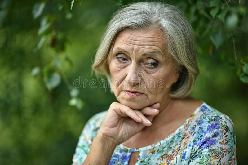 Nice sad old woman. On the spring background royalty free stock photo