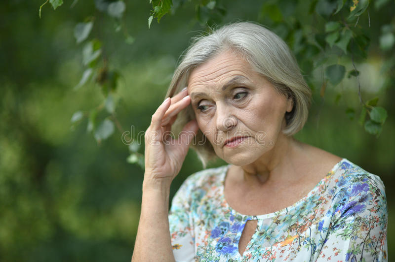 Nice sad old woman. On the spring background stock image