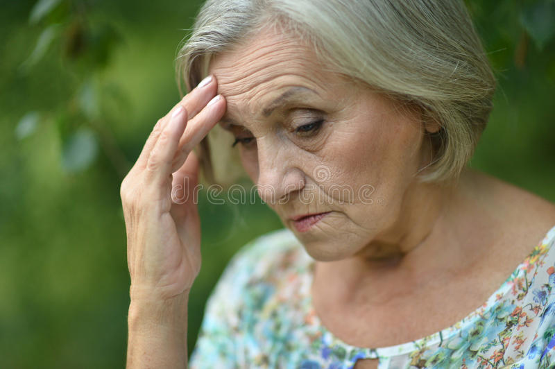 Nice sad old woman. On the spring background royalty free stock photography