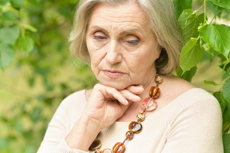 Nice sad old woman. On the spring background royalty free stock images