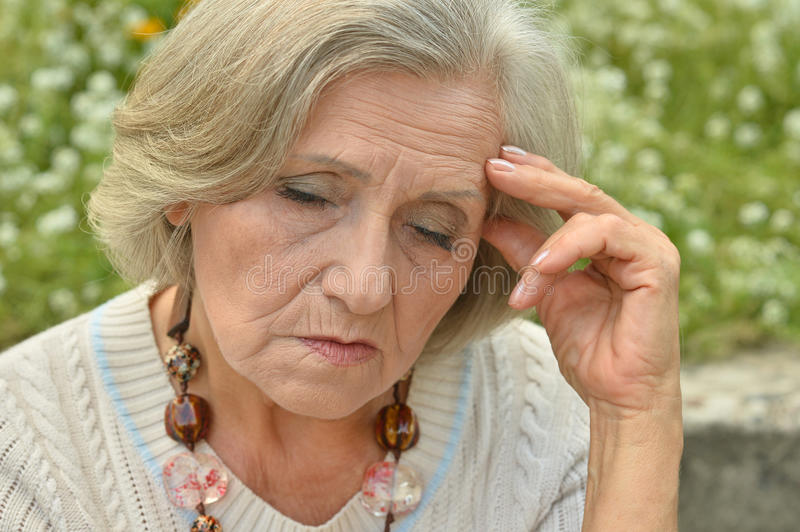 Nice sad old woman. On the spring background stock images