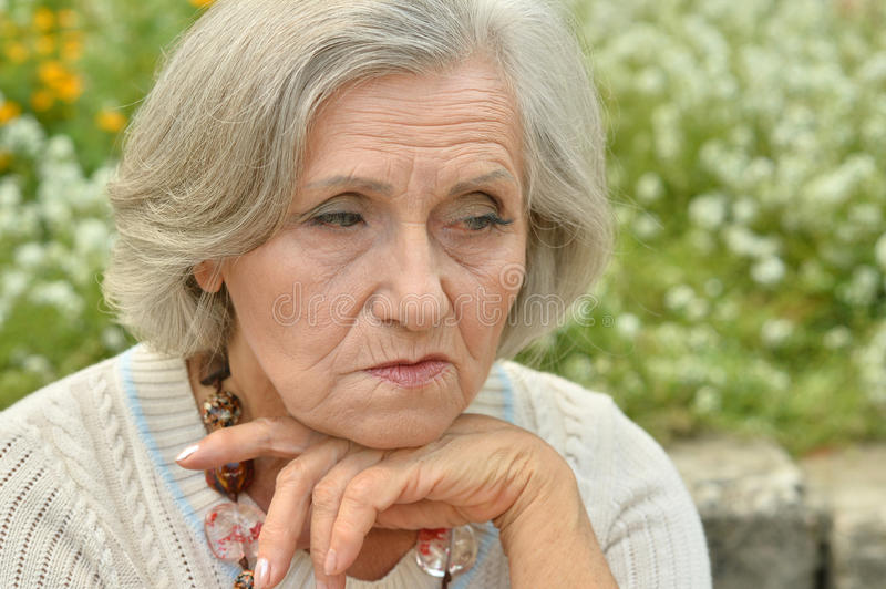 Nice sad old woman. On the spring background royalty free stock image