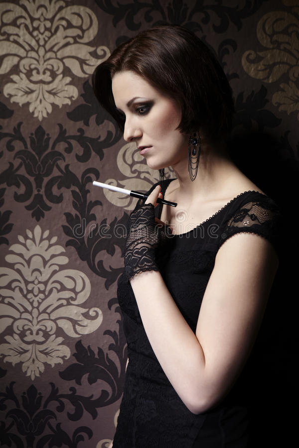 Nice but sad. Young woman on indoor location posing as drug addict. Female smoking cigarettes royalty free stock images