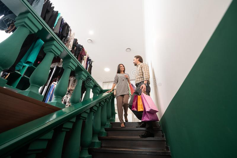 Nice-se den manliga hjälpande långhåriga förtrollande bländande kvinnan med shoppingpackar arkivbild