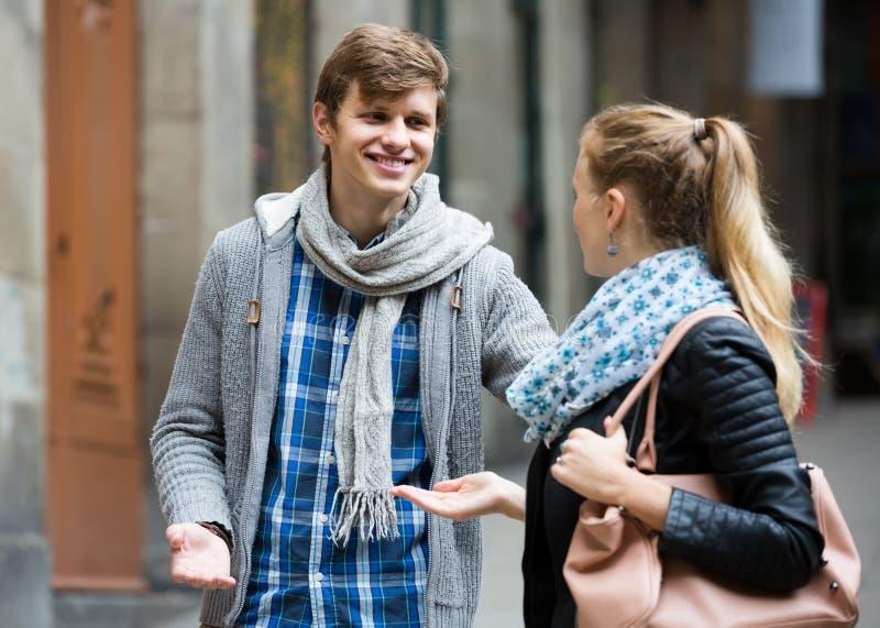 Nice-se den manliga studenten som jagar den nöjda flickan på utomhus- datum arkivfoto