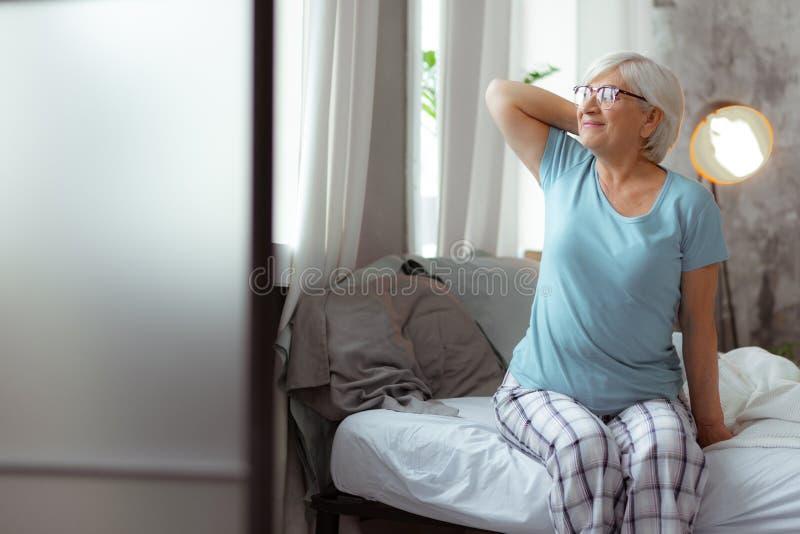 Nice-se kvinnan som ser in i fönstret, medan sitta på säng arkivfoton