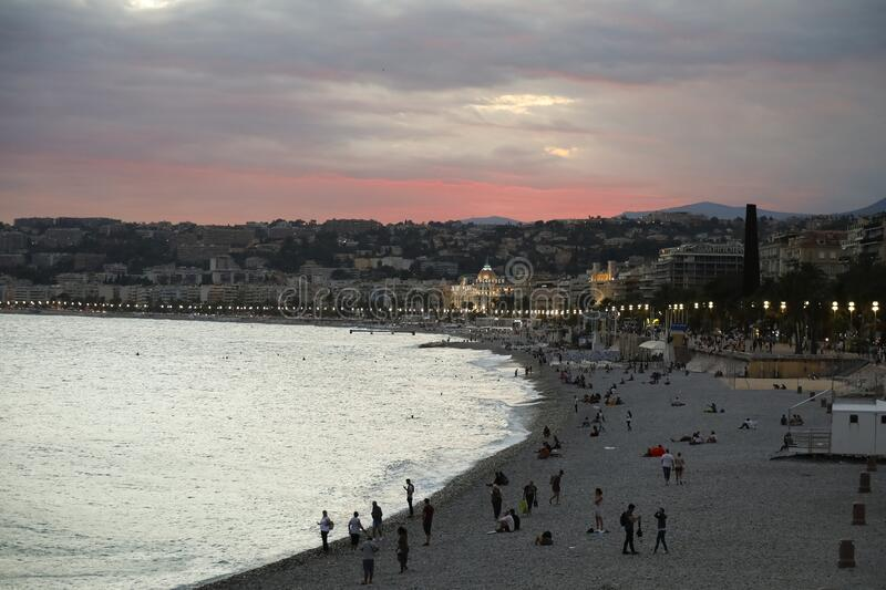 Nice is seen at late evening. Nice, France - September 24, 2018: People are still on the beach, but The Bay of Angels, Cote d`Azur is already seen at late stock image
