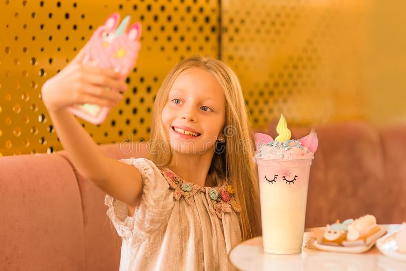 Nice selfie. little girl spend free time in cafe. Natural beauty. Childhood happiness. make selfie on unicorn phone stock photography