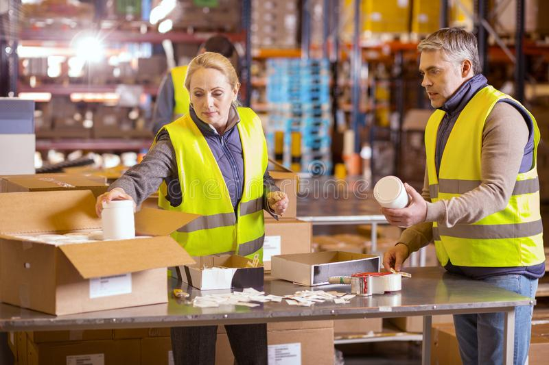 Nice serious people packing boxes royalty free stock photography