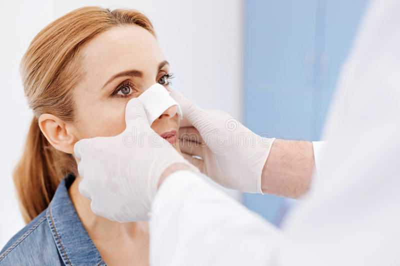 Nice serious woman undergoing cosmetic surgery. Perfect nose. Nice serious attractive women visiting a hospital and undergoing cosmetic surgery while wanting to royalty free stock photo