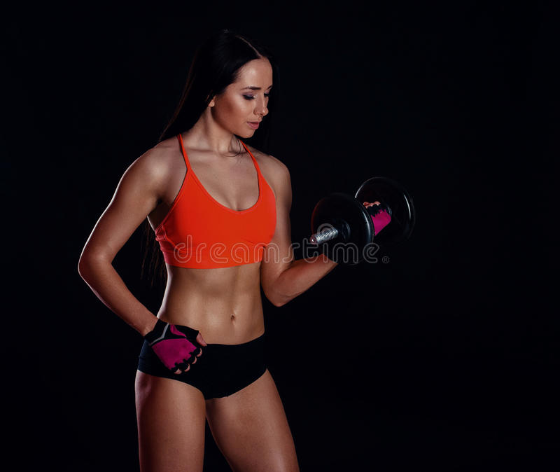Nice girl doing workout with dumbbells isolated over black background. Athletic young woman do a fitness workout with weights stock photo