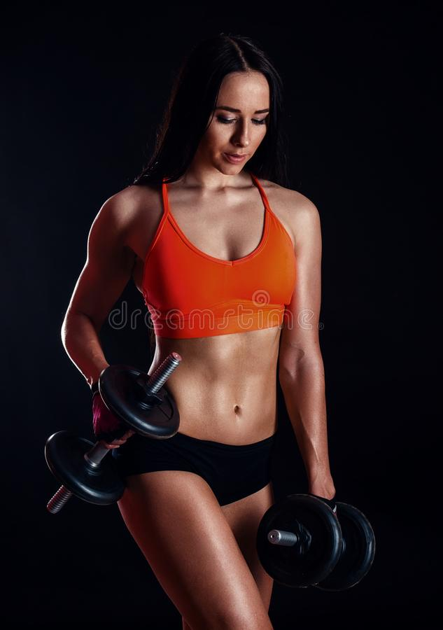 Nice girl doing workout with dumbbells isolated over black background. Athletic young woman do a fitness workout with weights.  royalty free stock images
