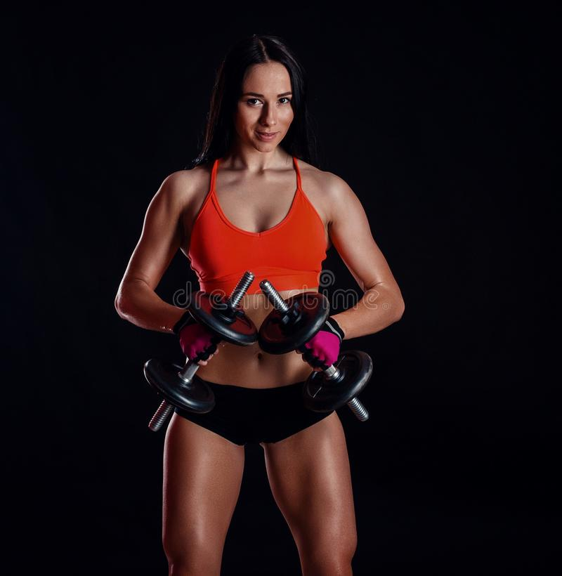 Nice girl doing workout with dumbbells isolated over black background. Athletic young woman do a fitness workout with weights royalty free stock photography