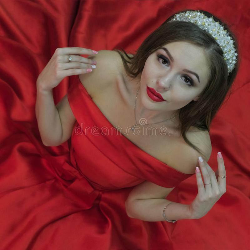 Nice girl in red dress and white tiara sits on the floor and holds fingers on her shoulders. View from above. Square frame fo stock photo