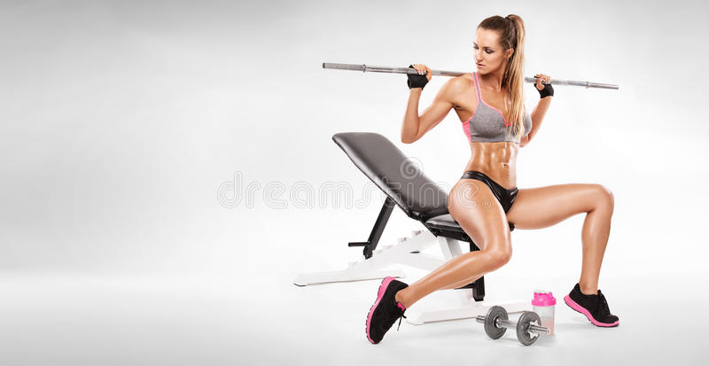 Nice woman sitting on a bench and workout with dumbbell royalty free stock image