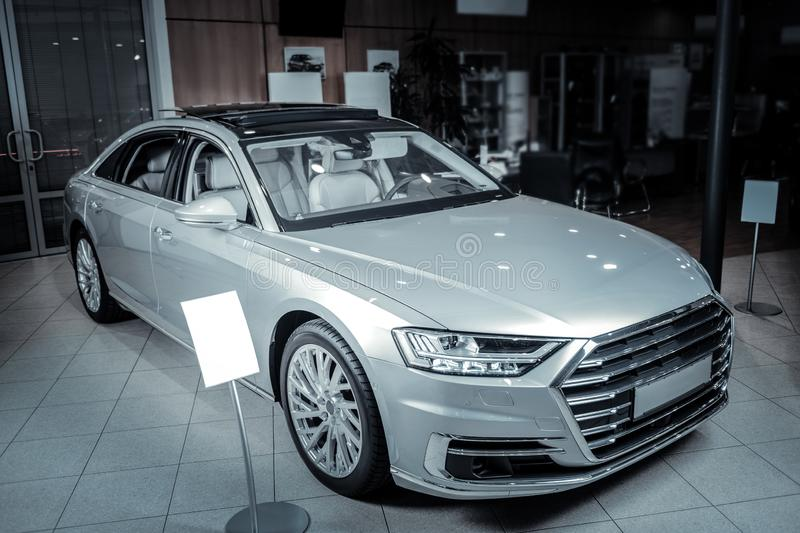 Nice silver car standing in light spacious salon of car dealers. Silver car. Nice silver car standing in light spacious salon of car dealers waiting for its new royalty free stock photography