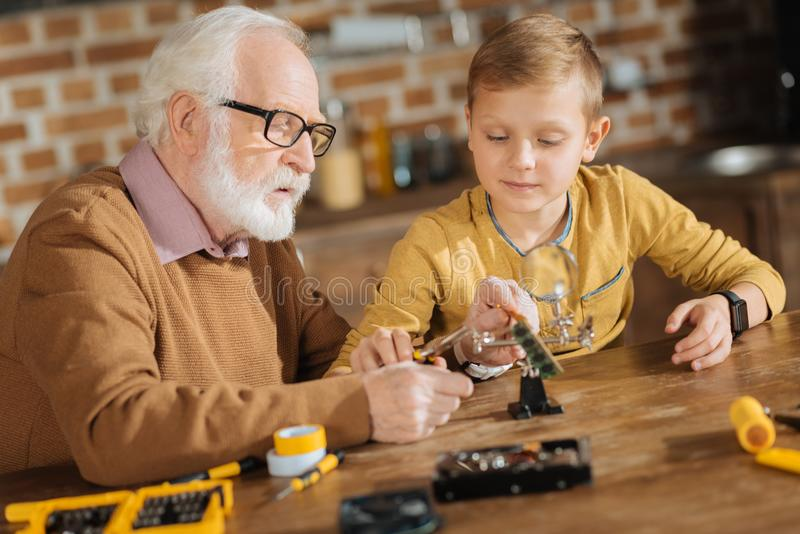 Nice smart grandfather and grandson fixing objects together royalty free stock images