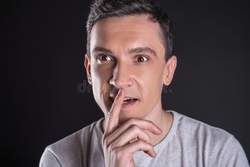Nice smart man som sätter hans finger till munnen fotografering för bildbyråer