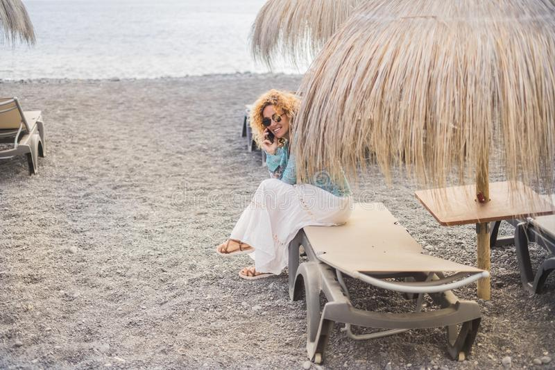 Nice smiled curly blonde hair lady on vacation sitting on a beach setas under umbrella tropical style use modern smartphone to. Stay connected with friends at royalty free stock photo