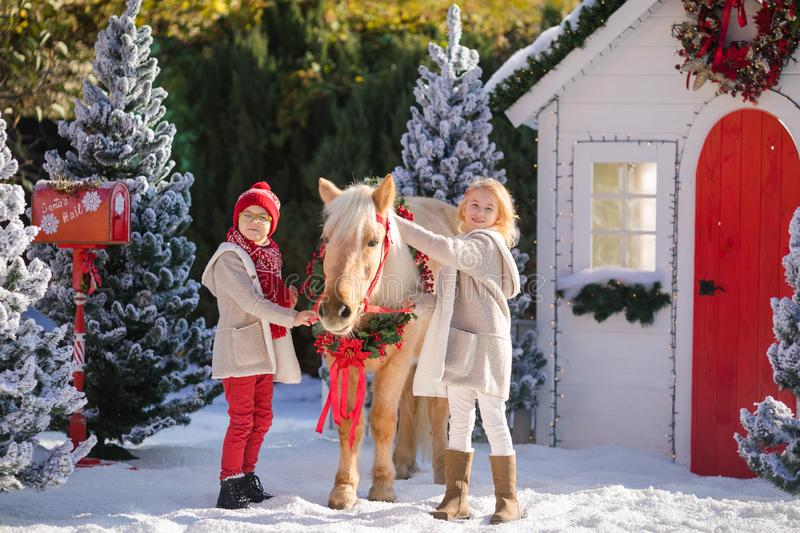 Nice smiling children and adorable pony with festive wreath near the small wooden house and snow-covered trees. New Year and Christmas time stock photo