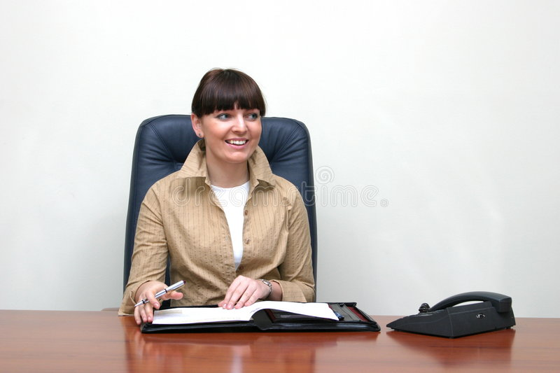 Nice,smiling secretary. Adult white and young smiling female at work in a smart beige jacket and a white blouse who is looking aside and sitting behind a brown royalty free stock photography