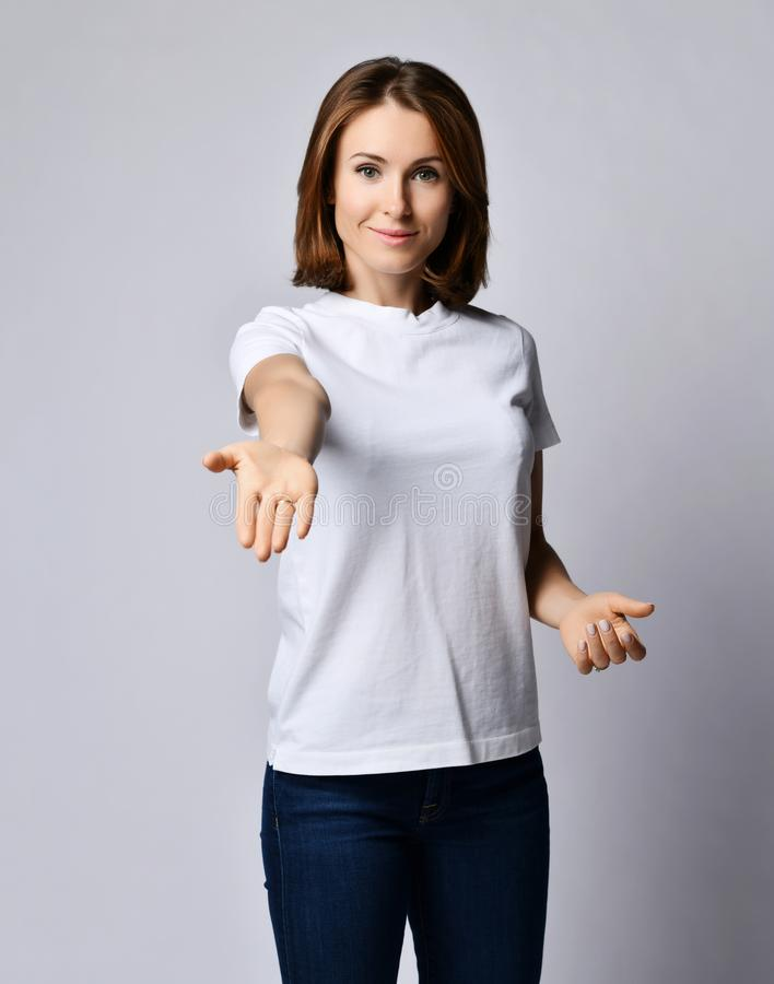 Nice smiling woman in white t-shirt and blue jeans holds out her hand with open palms like is going to help or gives us something stock photo