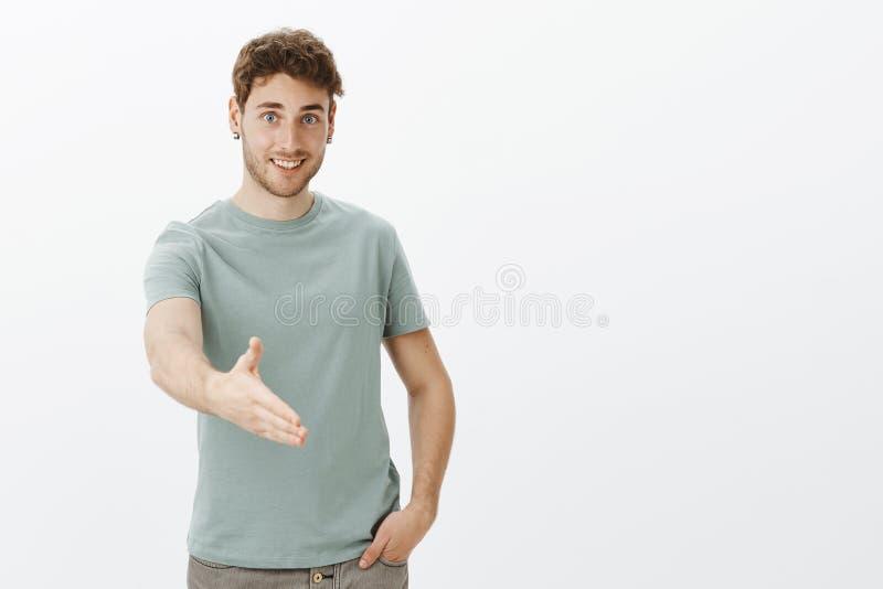 Nice som möter dig, hopp att gå Stående av den vänliga lyckliga unga mannen i tillfällig t-skjorta som rymmer handen i fack och fotografering för bildbyråer