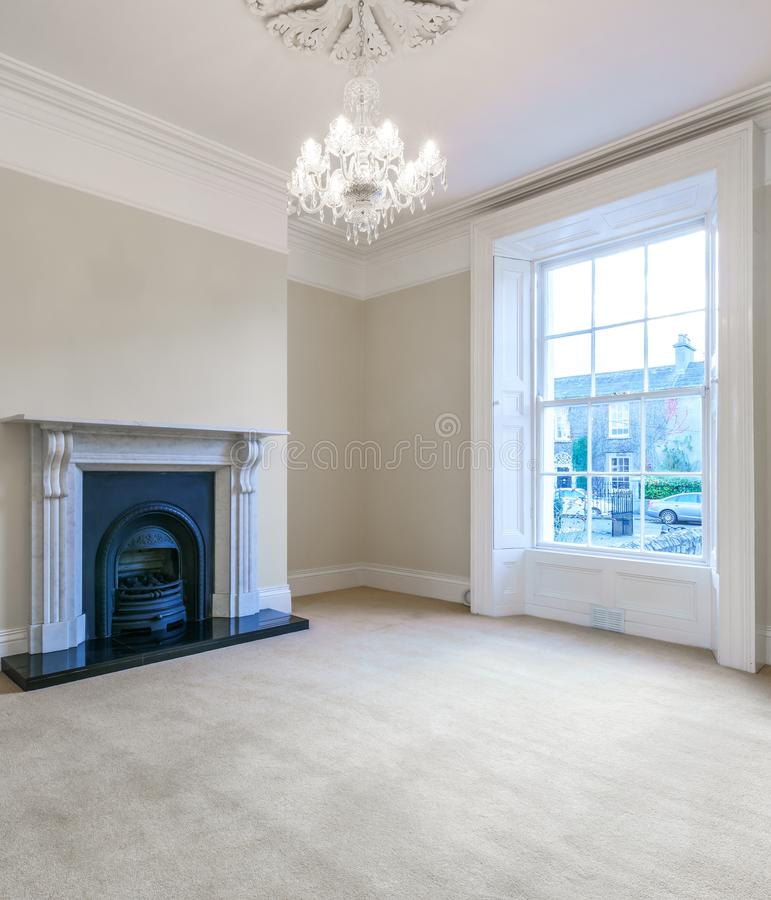 Nice spacious living room with a large window and stylish fireplace stock image