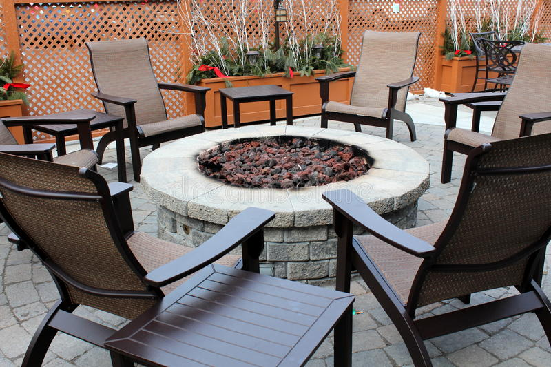 Nice stone fireplace with outdoor chairs. Gray stone fireplace with outdoor chairs and tables gathered around,where people can sit together for an intimate stock photos