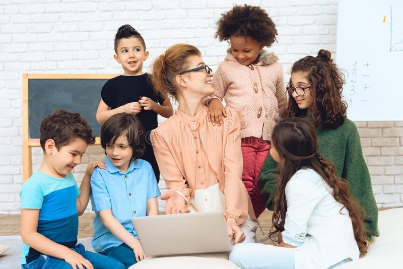 Nice teacher sits with school children who have surrounded her and are looking at laptop. stock photo