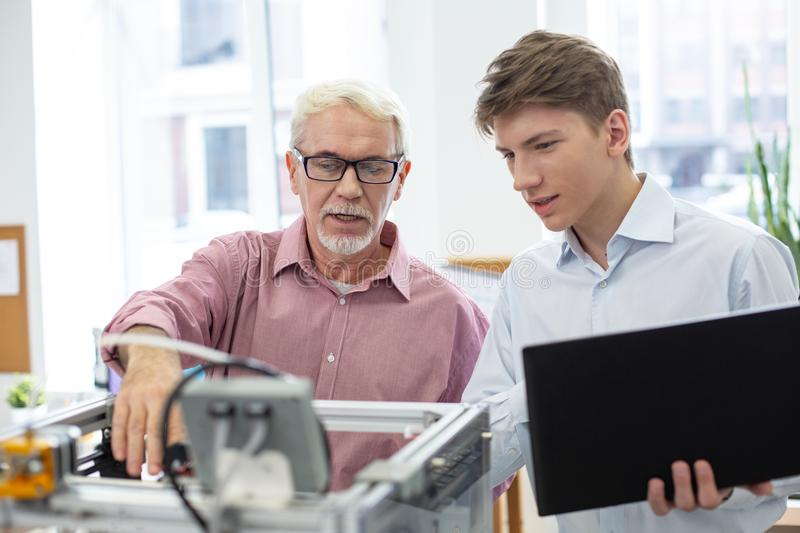 Pleasant senior engineer teaching about 3D printer royalty free stock images