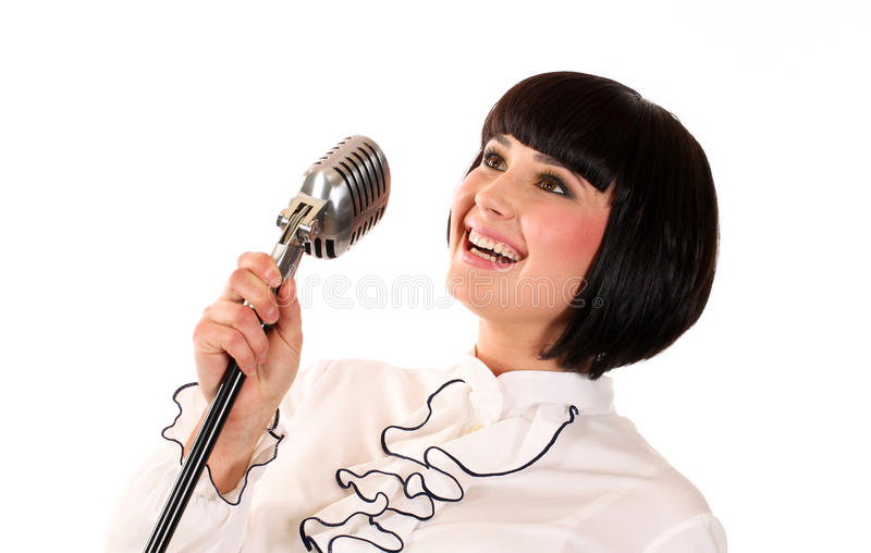 Nice teen girl singing with a microphone isolated. Lovely royalty free stock photo