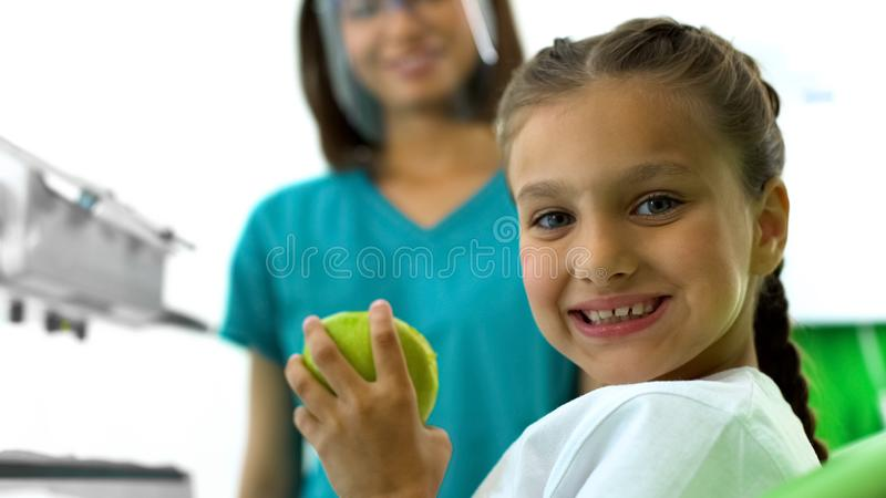 Nice teenage girl holding green apple and smiling at camera, children teeth care stock images