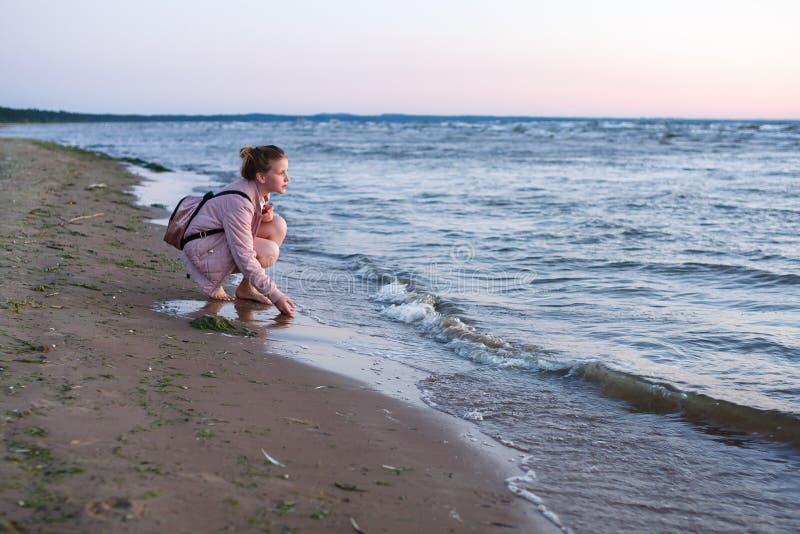 Nice teenager girl is walking near the sea at the seashore at th royalty free stock photos