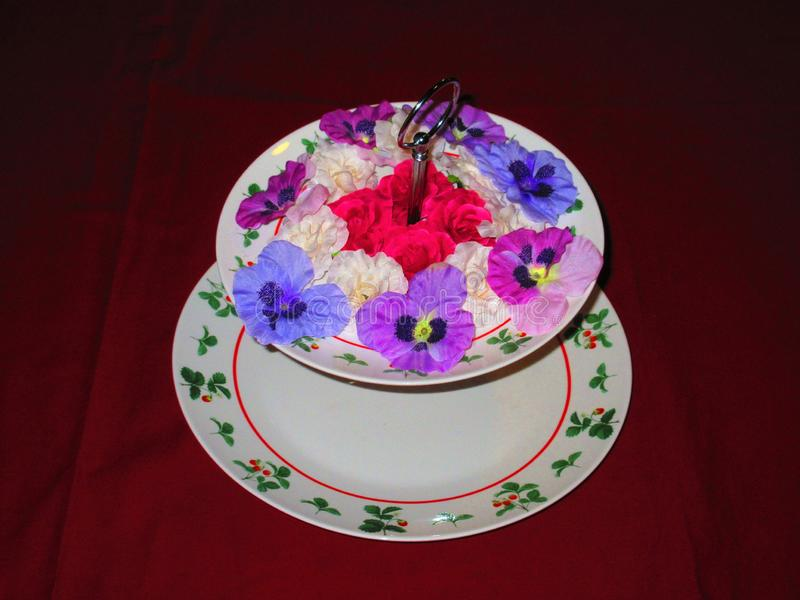 It is nice to decorate the dish whit silk flowers when the bottom part is for sweet biscuits stock images
