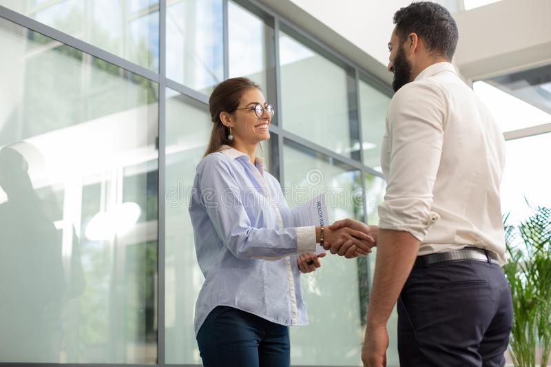 Joyful young female person communicating with colleague. Nice to meet you. Cheerful young men standing in semi position and welcoming new coworker stock images