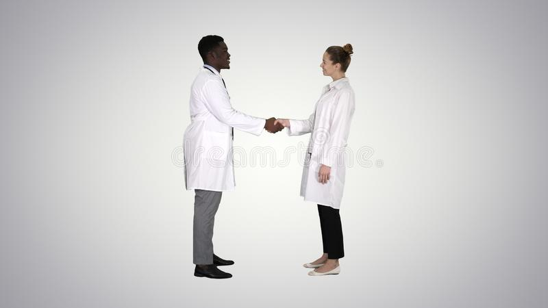 Nice to meet you Doctors meet and shake hands on gradient background. royalty free stock photo