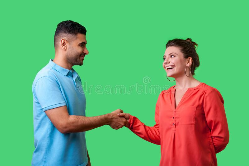 Nice to meet you! Portrait of happy young couple in casual wear shaking hands. isolated on green background stock photo