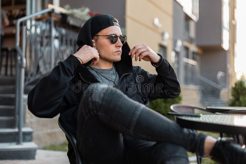 Nice urban young hipster man in black hoodie in stylish sunglasses in vintage jeans in a black cap resting stock photography