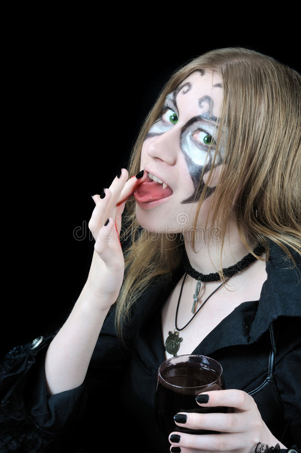 Nice vampire girl licks blood from her finger. On black background royalty free stock images