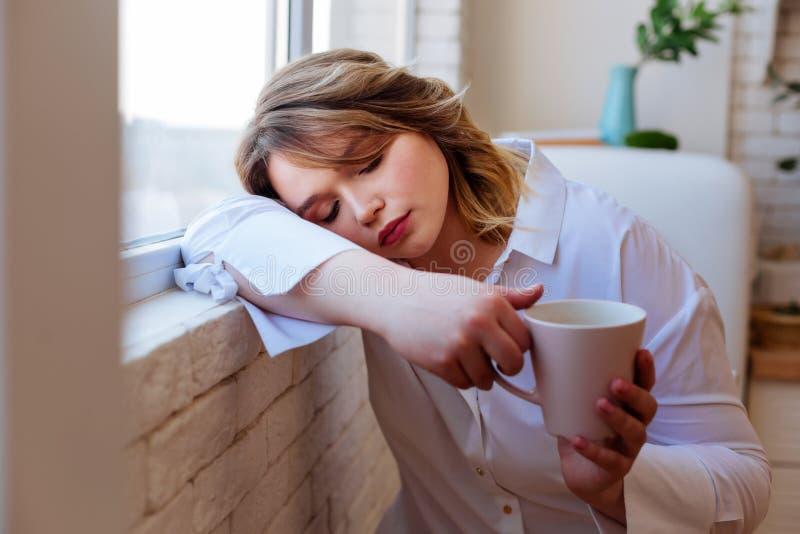 Nice vermoeide vrouw die in slaap met een kop thee vallen stock afbeeldingen