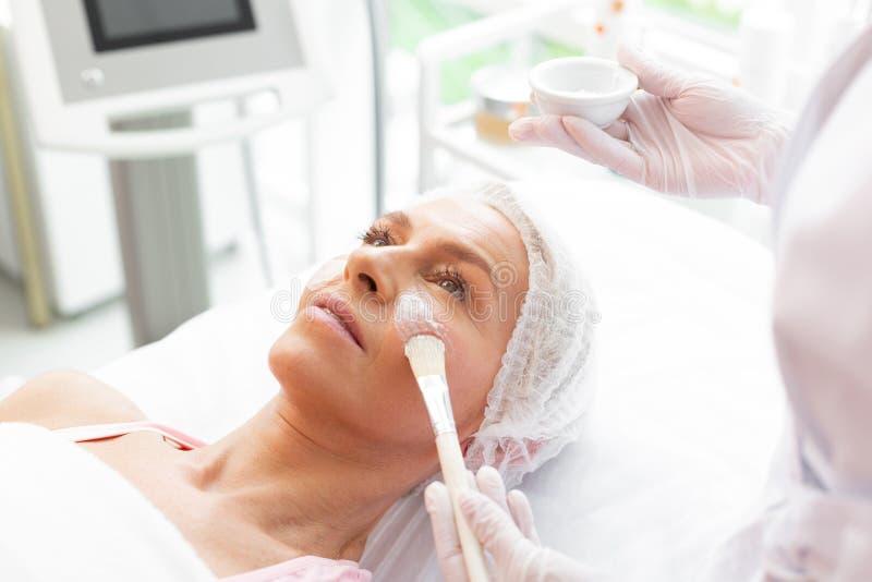 Nice verouderde vrouw die een gezichts toegepast masker hebben stock afbeelding