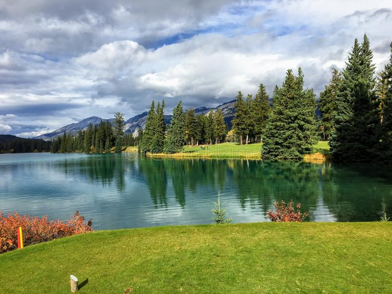 A nice view of a difficult par 4 on a golf course that demands your first drive off the tee carry a large lake. In order to hit the fairway. The golf hole is by royalty free stock photo
