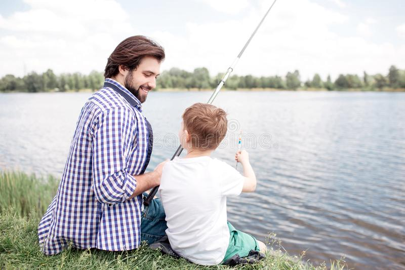 Nice view of happy son and dad sitting together at river shore. Guy is looking at his son and fishing. Boy is looking at stock image