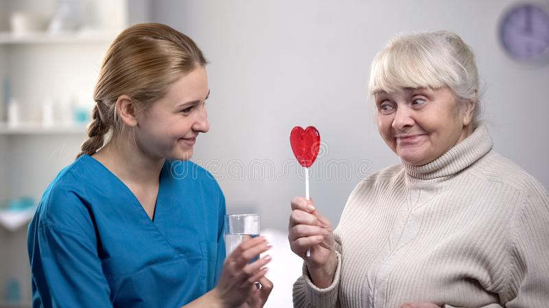 Nice volunteer giving glass of water to funny elderly woman holding lollipop royalty free stock image