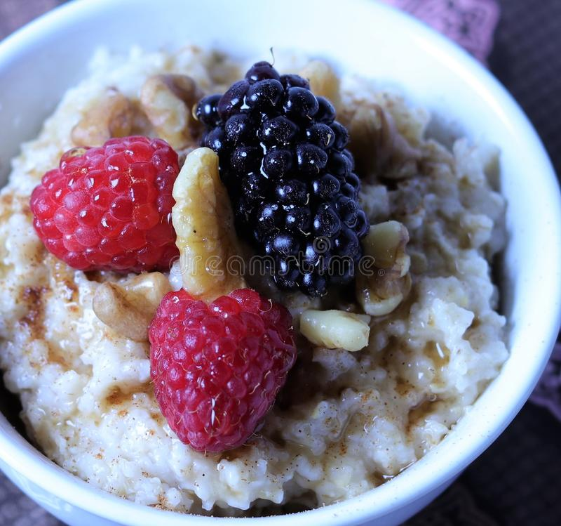 A nice warm bowl of oatmeal, topped with raspberries and blackberries with walnuts and drizzle of maple syrup royalty free stock photos