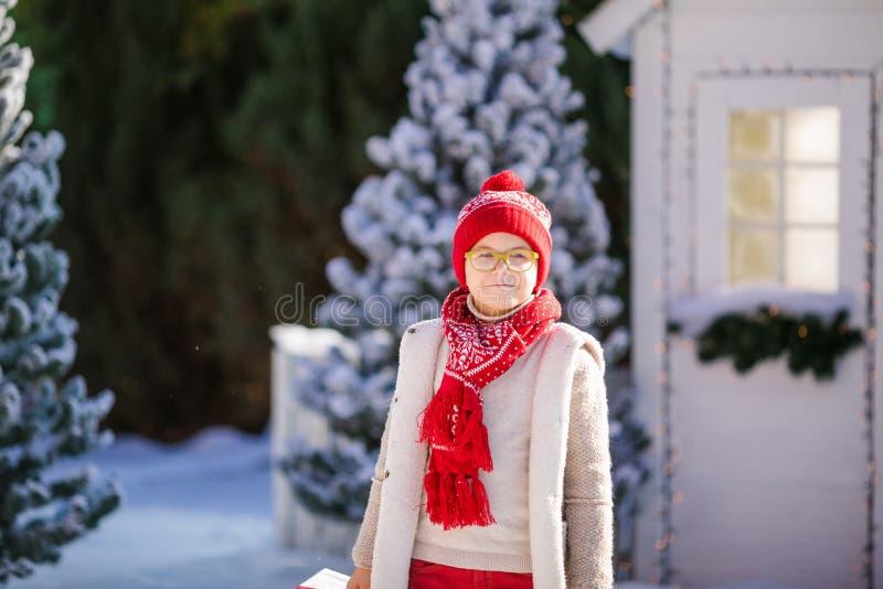 Nice weinig jongen met rode hoed en groene glazen vindt een groot heden dichtbij de Kerstboom royalty-vrije stock fotografie