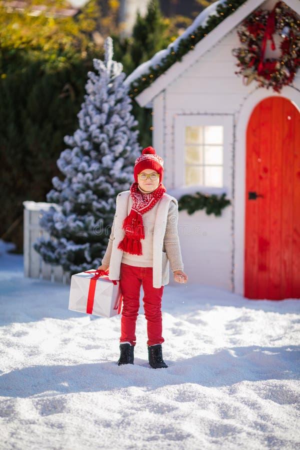 Nice weinig jongen met rode hoed en groene glazen vindt een groot heden dichtbij de Kerstboom stock afbeeldingen