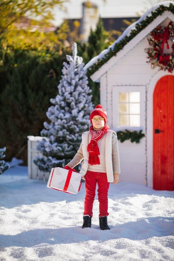 Nice weinig jongen met rode hoed en groene glazen vindt een groot heden dichtbij de Kerstboom royalty-vrije stock foto